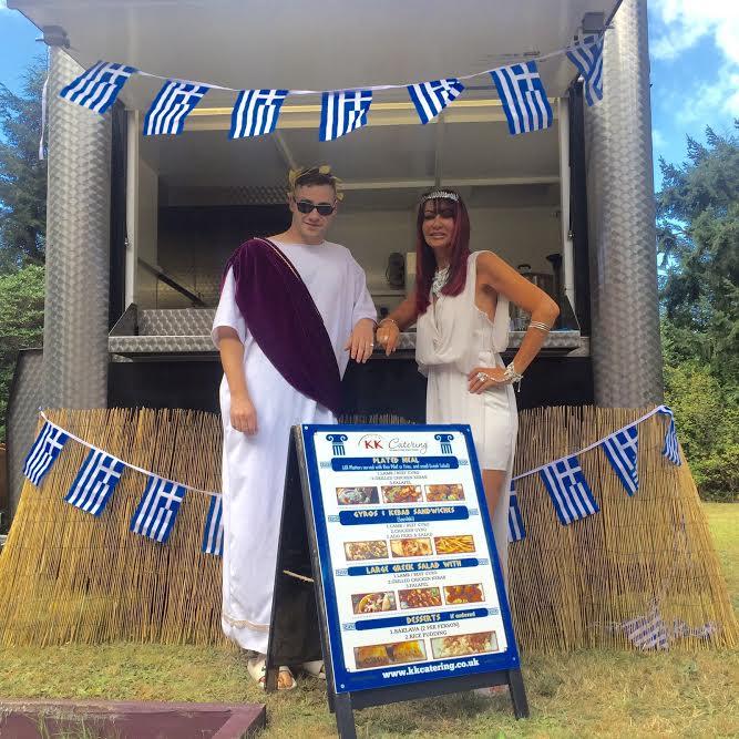 couple standing in front of Greek Souvlaki hut