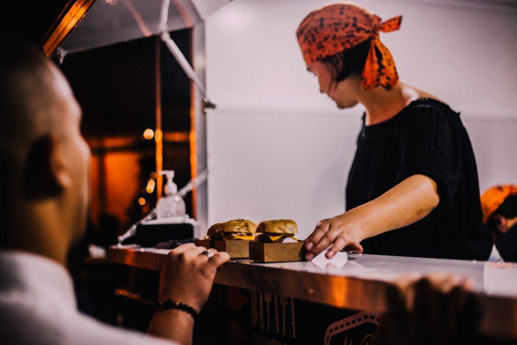 team member serving burgers from burger van