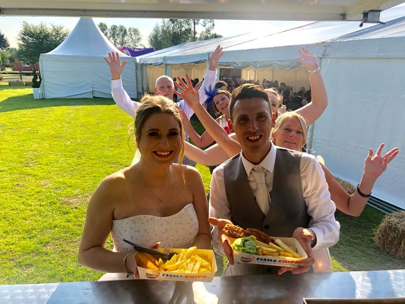 bride and groom with fish and chips at their wedding breakfast