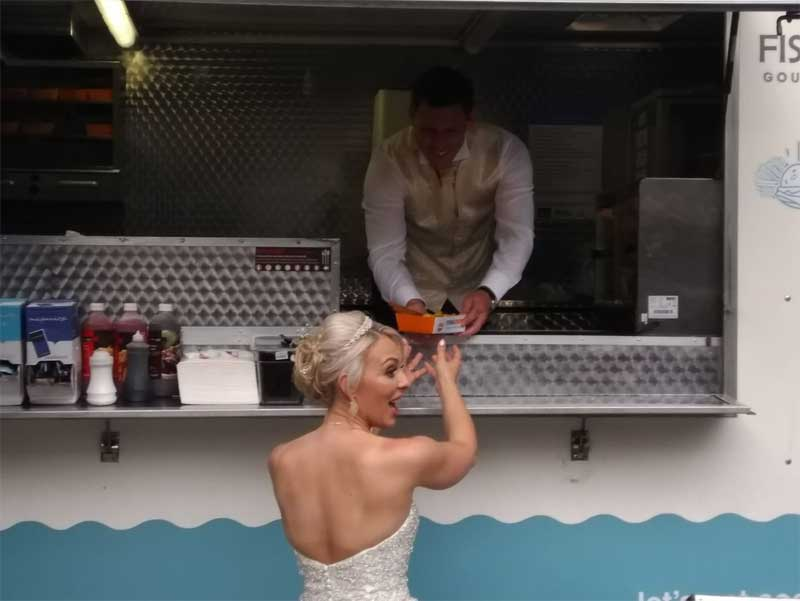 bride being served fish and chip by husband at fish and chip van
