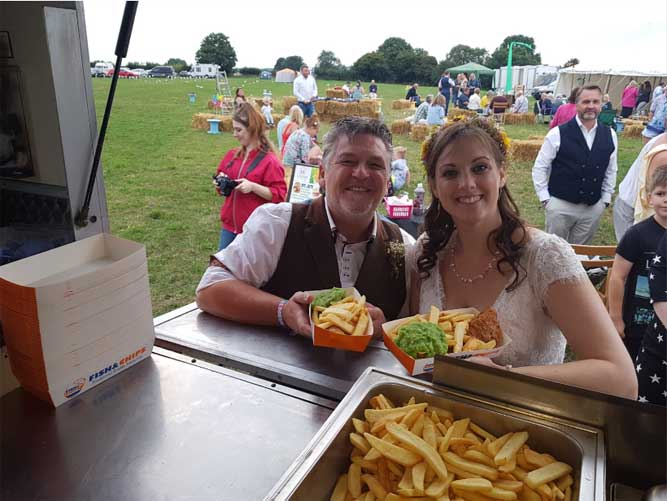 bride and groom with fish and chips at there wedding