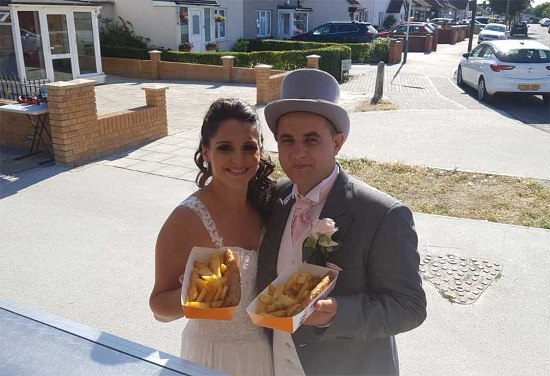 bride and groom with fish and chips on wedding day