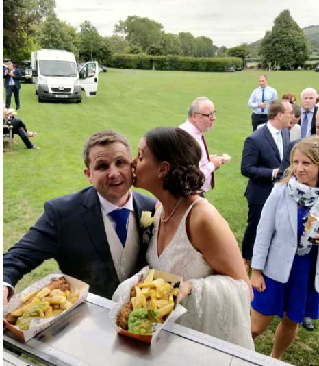 bride kissing groom at fish and chip van