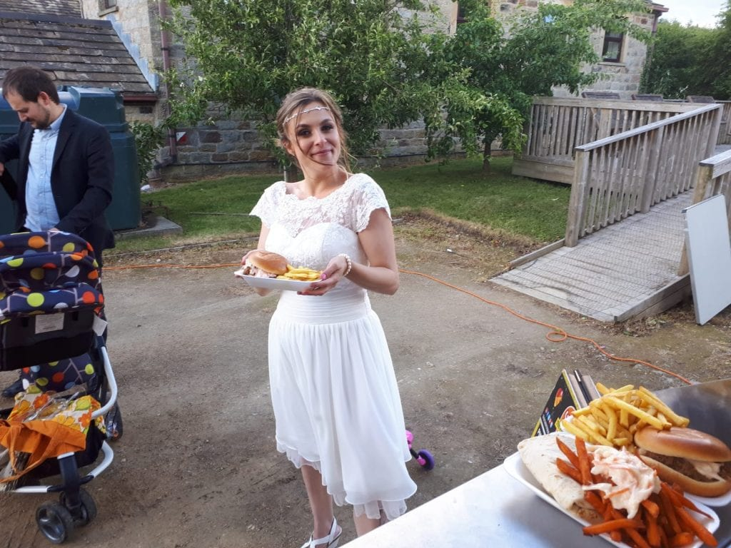 Bride holding a plate with burger and fries