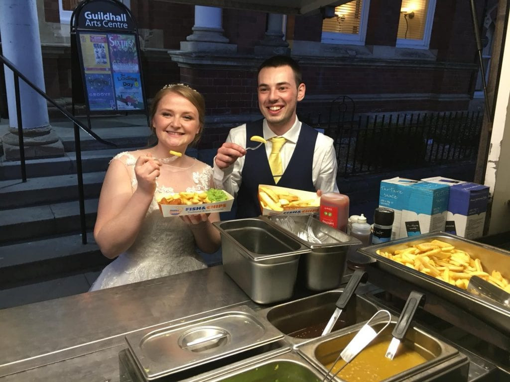 Couple celebrate with fish and chips wedding food to keep the cost down per head